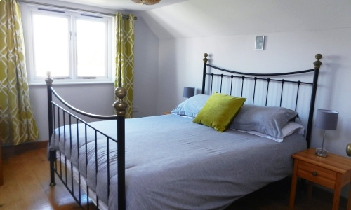 Bedroom interior photo with wooden floor, geometric pattern curtains, iron bedstead and pale grey bedlinen