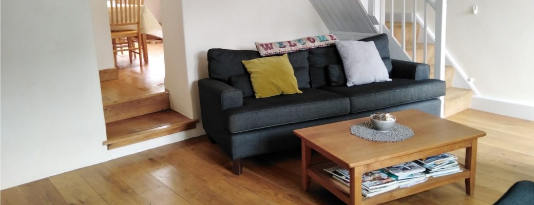 Interior picture of lounge with wood floor, grey sofa