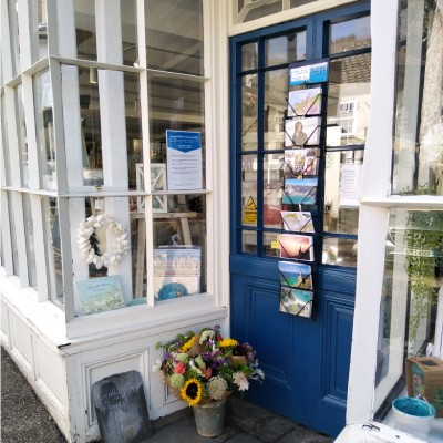 Shop front door with postcard rack and florist's bucket with flowers