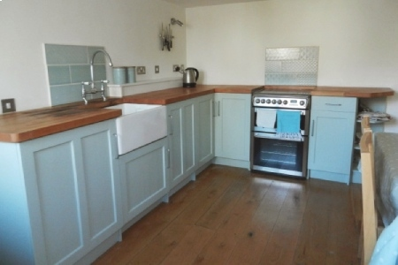 Photo of kitchen with wooden work tops, oak floors, painted wooden cabinets and a butler sink.