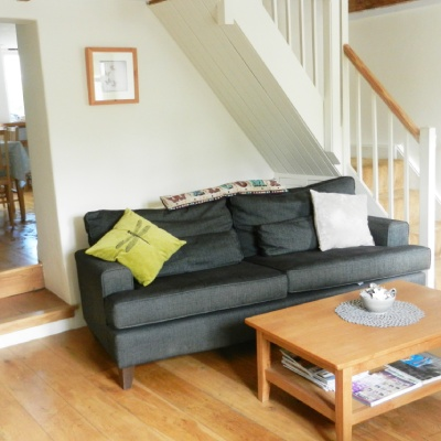 interior shot of lounge with grey sofa, scatter cushions, oak floorboards