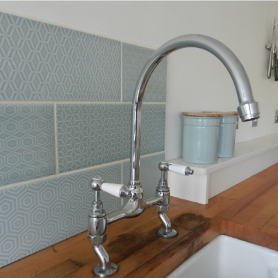 Kitchen mixer taps with geometric tile splashback